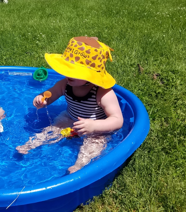 Better Beauty Vermont playing in kiddie pool with giraffe hat